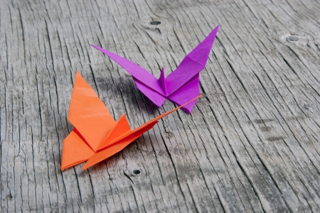 Pink and orange Origami butterflies on vintage wood background