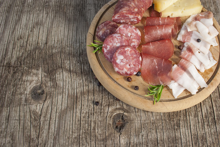 Cutting board with traditional Italian cold cuts: salami, dried beef, bacon and cheese isolated on rustic background Stock Photo