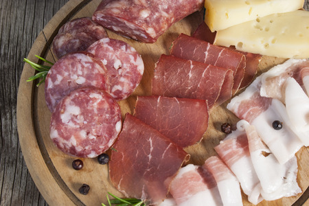 Breadboard detail with traditional Italian cold cuts: salami, dried beef, bacon and cheese isolated on rustic background