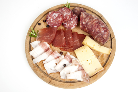 Cutting board with traditional Italian cold cuts: salami, dried beef, bacon and cheese isolated on white background
