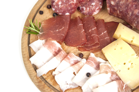 Breadboard detail with traditional Italian cold cuts: salami, dried beef, bacon and cheese isolated on white background Stock Photo