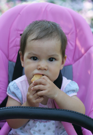 The portrait of the eight-months  girl seating in baby carriage and eating crouton photo
