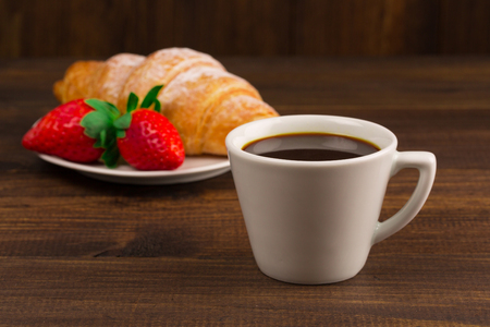 coffees: Continental breakfast with croissant, coffees and fresh strawberries.