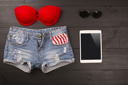 denim shorts: Summer womens accessories: red brassiere, denim shorts, tablet, sunglasses on wood background Stock Photo