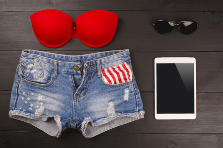 brassiere: Summer womens accessories: red brassiere, denim shorts, tablet, sunglasses on wood background Stock Photo