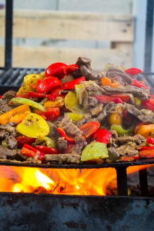 flesh eating animal: Food Beef bbq on grill with fire served with tomatoes and roast vegetables Stock Photo