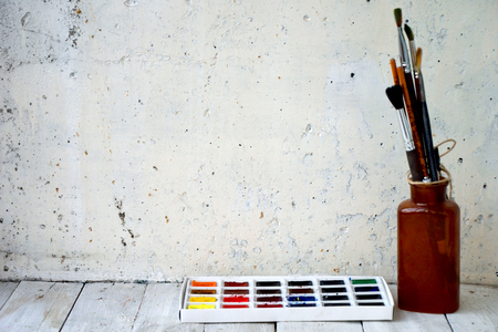 Watercolor and oil paints, brushes for painting, pencils, pastel crayon on white wall. Top view. Archivio Fotografico