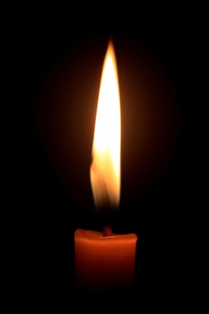 Close-up lit candles isolated black background
