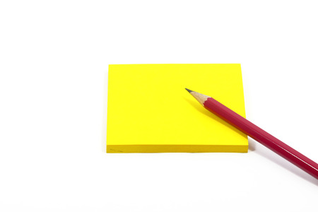 Yellow paper note with pencil on white background photo