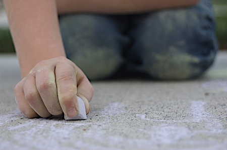 child drawing with purple sidewalk chalk with messy chalk on pants photo