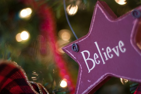 red star shaped believe ornament hanging on christmas tree Stock Photo