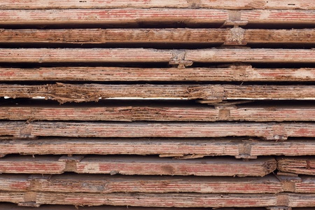Stacked used red form boards with chips and brackets