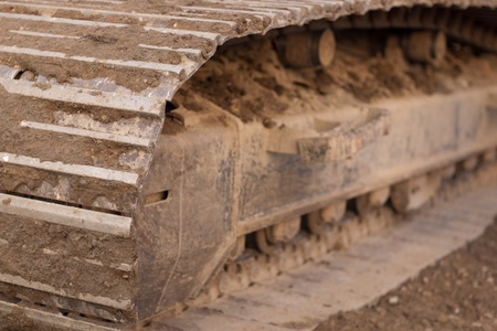 track of an excavator sitting on grass with dirt in the tracks
