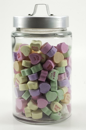 jar with lid filled with valentine hearts isolated on a white background