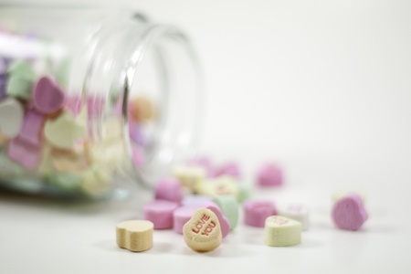 spilled jar of valentine hearts with love you in front