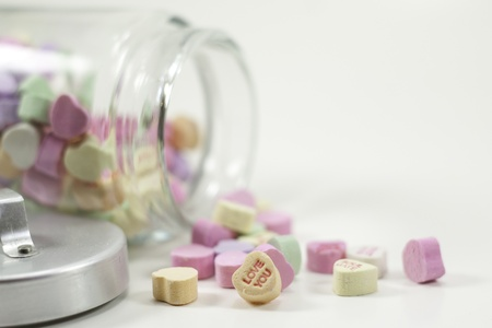 a jar of valentine hearts spilled isolated on white background