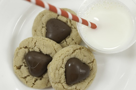 three cookies with chocolate hearts and glass of milk with a striped red straw view from above with white background