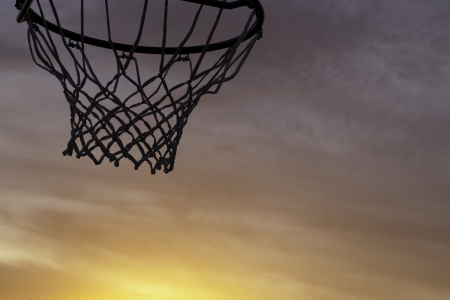 basketball hoop silhouette with an orange sunset