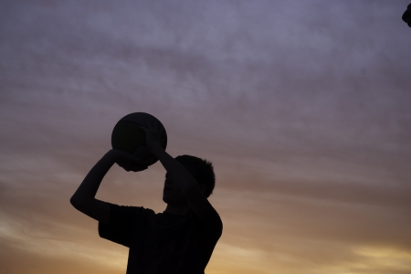boy shooting basketball silhouette with a sunset in background Stock Photo