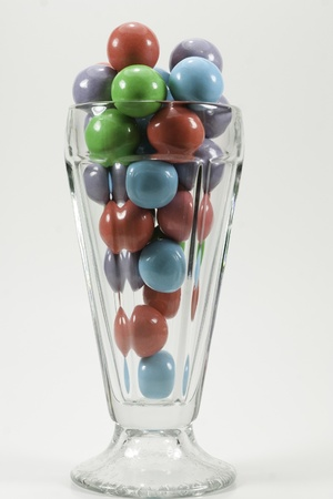 a sunday glass filled with colorful red, green, blue, and purple gumballs