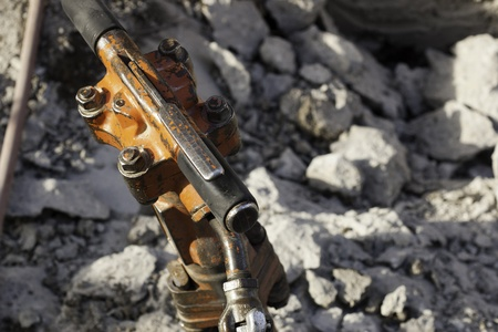 jack hammer used for breaking, chipping, and demolishing concrete with shallow dof and broken concrete in background