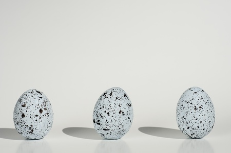 three blue eggs with black spots in a row isolated on white backgrond