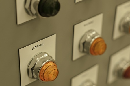 bright orange warning light on electrical panel shallow depth of field Stock Photo