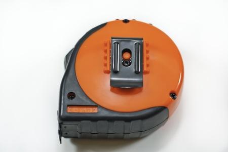 an orange tape measure isolated on white background Stock Photo