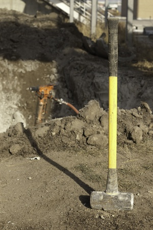 yellow sleg hammer on construction site with a jack hammer in the background Stock Photo