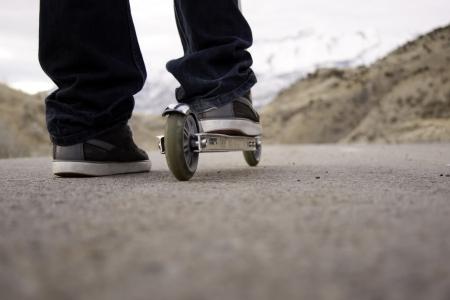 kind op scooter op de verharde weg met bergen op de achtergrond Stockfoto