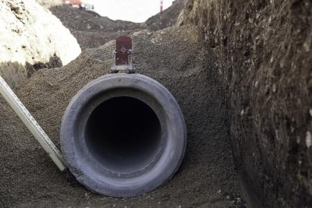 infraestructura: instalaci�n de tuber�a de hormig�n en el sitio de construcci�n con el nivel y relleno