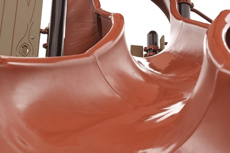 bright red slide curved winding in park for children viewed from the bottom