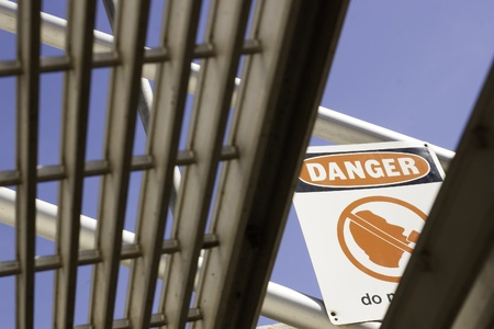a danger sign as viewed from under the stairs