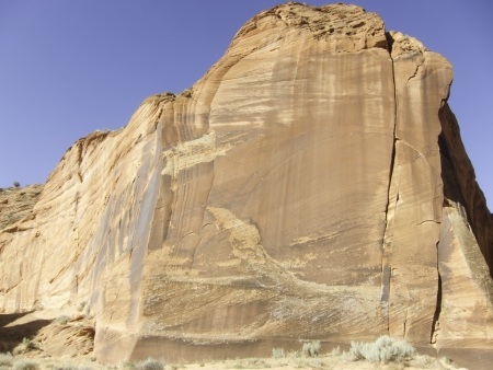 tall sandstone cliff with a bright blue sky in southern Utah Stock Photo