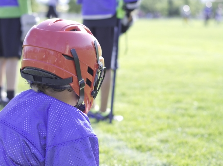 Lacrosse player watching from the sidelines.