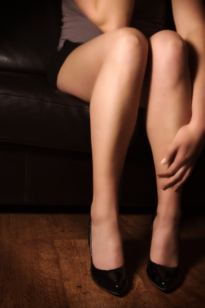 Young woman   girl sitting lonely on a leather couch  Holding her hand at her leg  photo