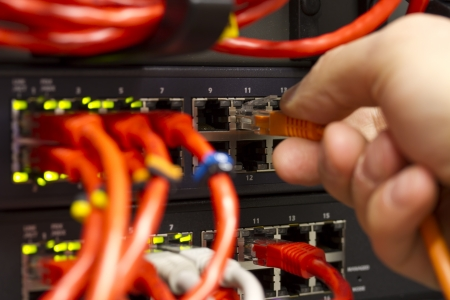 Close up of a IT consultant inserting   connecting a network cable into a switch
