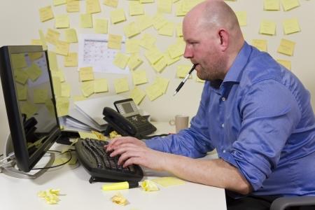 oficina desordenada: Un empleado de oficina de trabajo duro con mucho que ver la oficina Sucias