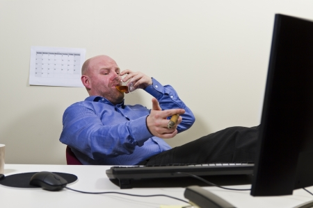 A businessman   office worker celebrating achievement with a cigar and congac at the office  photo
