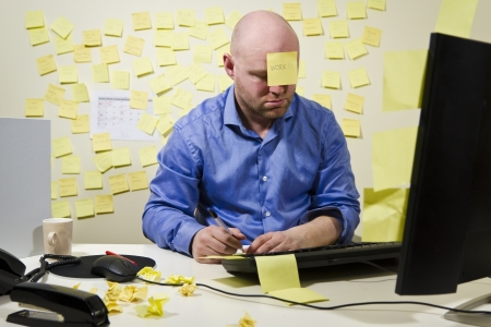Office worker   businessman with too much work to do  Many notes in the background and one post-it at the forehead