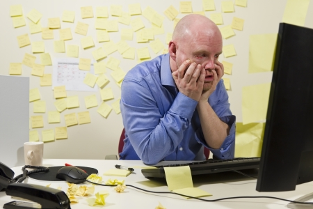 banging: A frustrated office worker looking at his computer monitor  Stock Photo