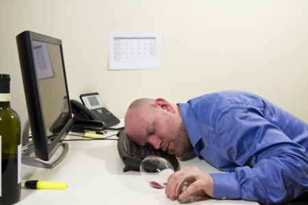 A drunk businessman   office worker sleeping at his computer keyboard  Stock Photo