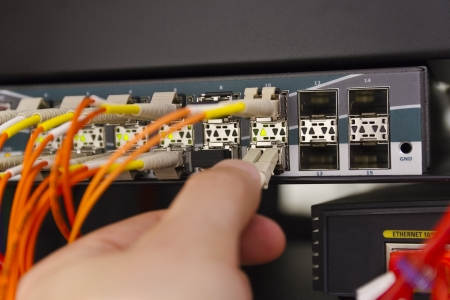 fiber cable: Insert a fiber cable into a switch in datacenter