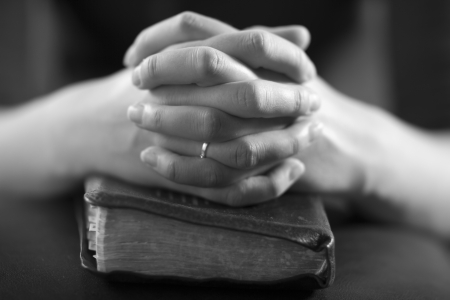 woman praying: Woman folding hands over her bible and praying to God  Stock Photo