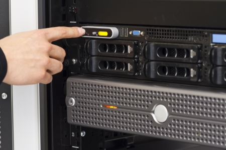 A close-up of a IT engineer   technician power on   turn on a server in a rack  Shot in a data center  photo