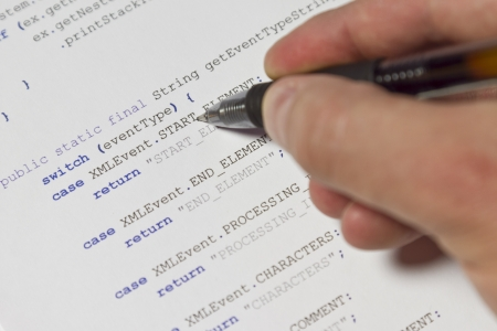 stylesheet: A programmer   man pointing with his pen at Java computer code  Software   application program code  XML parser