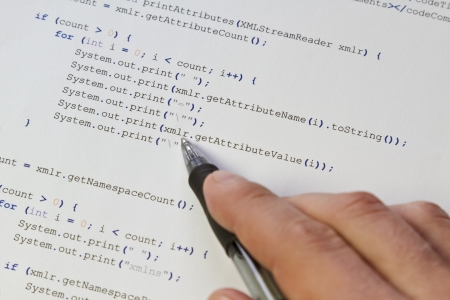 A programmer   man pointing with his pen at software computer code  Software   application program code  XML parser Stock Photo - 19198390