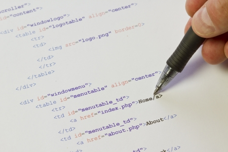 A programmer   man pointing with his pen at HTML code for a web page Stock Photo - 19198231