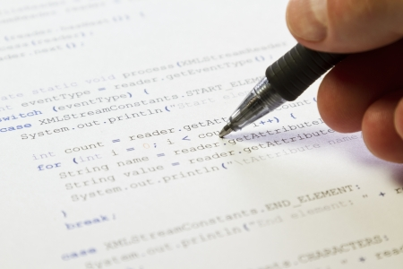 A programmer   man pointing with his pen at software computer code  Software   application program code  XML parser Stock Photo - 19198013