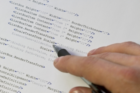 A programmer   man pointing with his pen at software computer code  Software   application program code  XML parser Stock Photo - 19198258